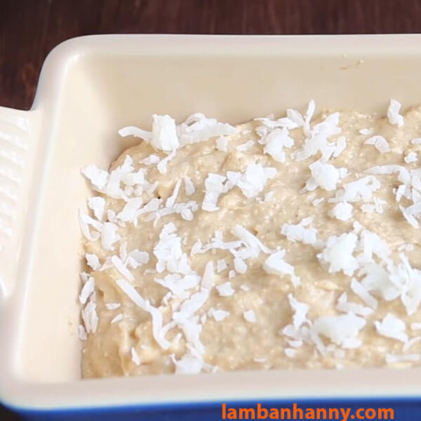 Cho hỗn hợp bột vào khuôn và rắc thêm lớp dừa bào lên trên